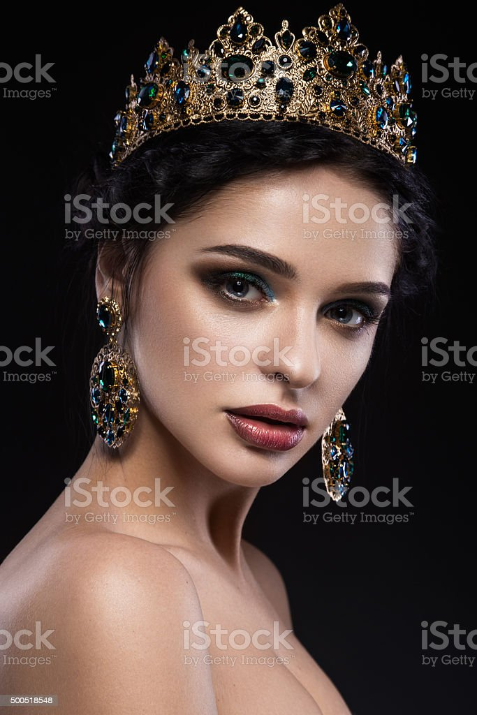 Beautiful brunette girl with a golden crown, earrings and professional stock photo
