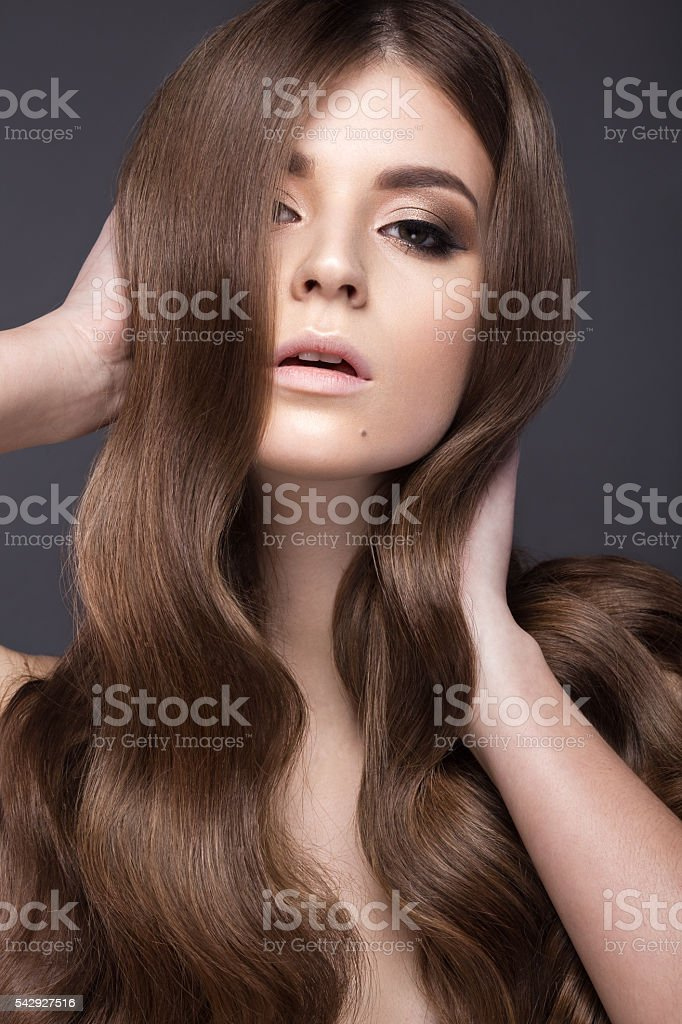 Beautiful brunette girl with a perfectly curls hair and classic stock photo