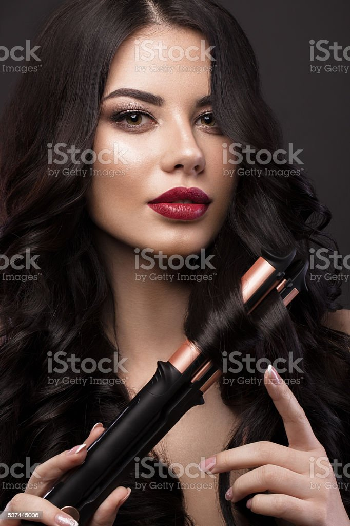Beautiful brunette girl with a perfectly curls hair, curling and stock photo