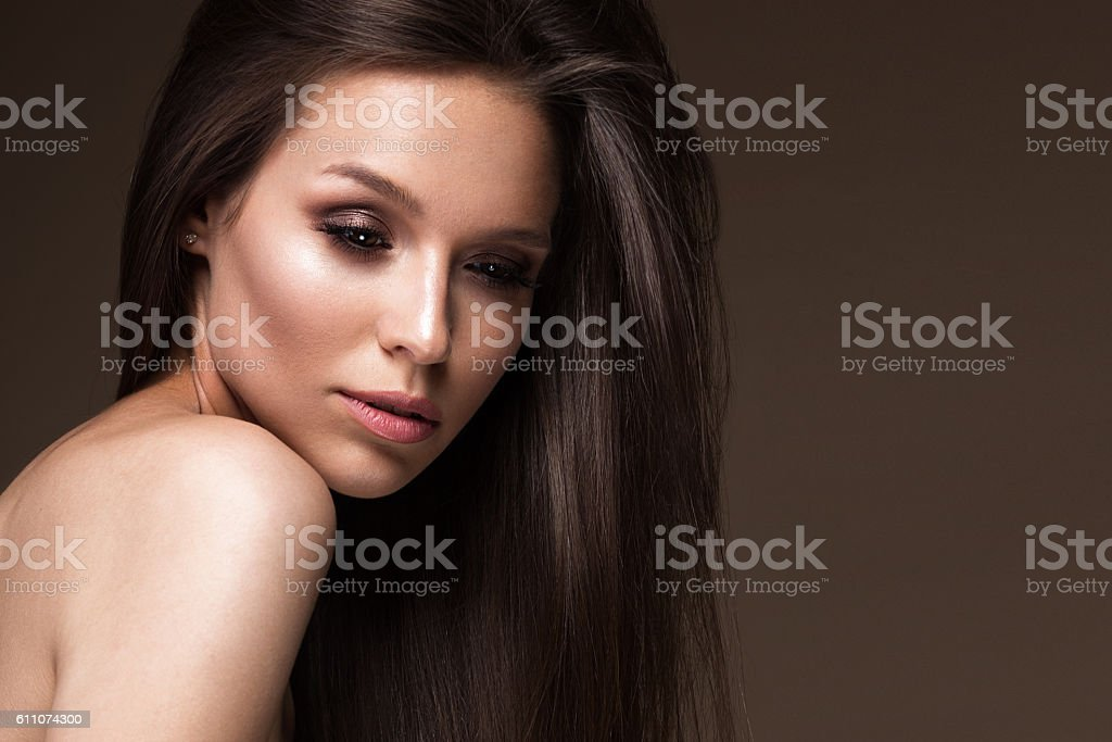 Beautiful brunette girl with a perfectly smooth hair, and classic stock photo
