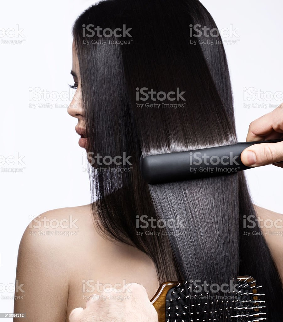 Beautiful brunette girl with a perfectly smooth hair, curling and stock photo