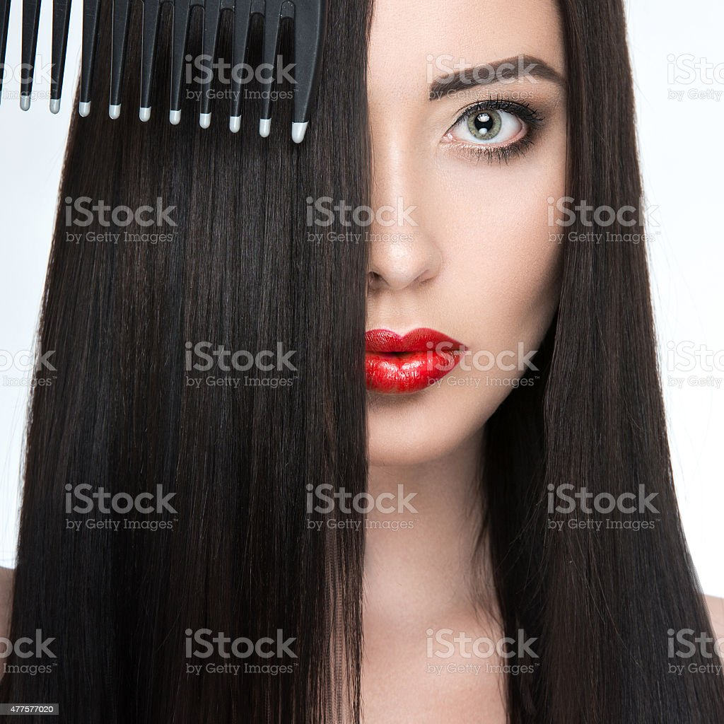 Beautiful brunette girl with a perfectly smooth hair, hairbrush and stock photo