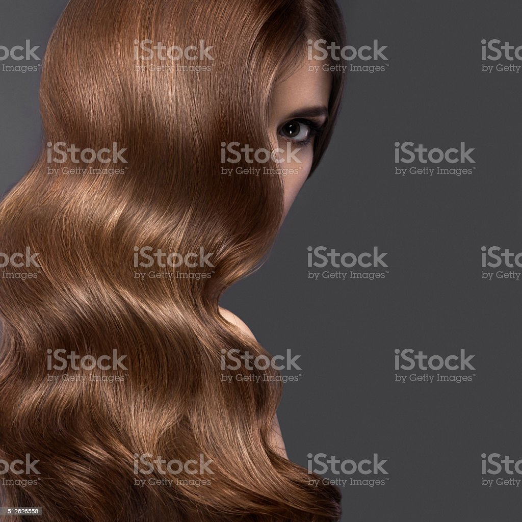 Beautiful brunette girl with perfectly curls hair and classic make-up. stock photo