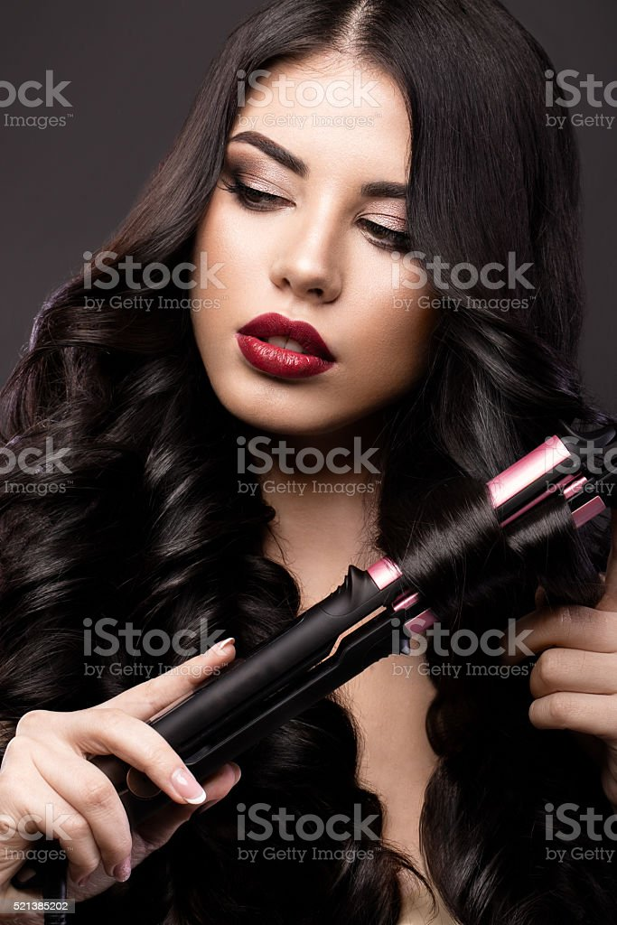 Beautiful brunette girl with perfectly curls hair, curling, classic make-u stock photo