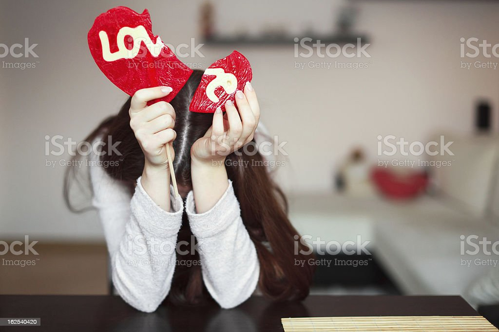 Beautiful brunette holding two parts of broken heart royalty-free stock photo
