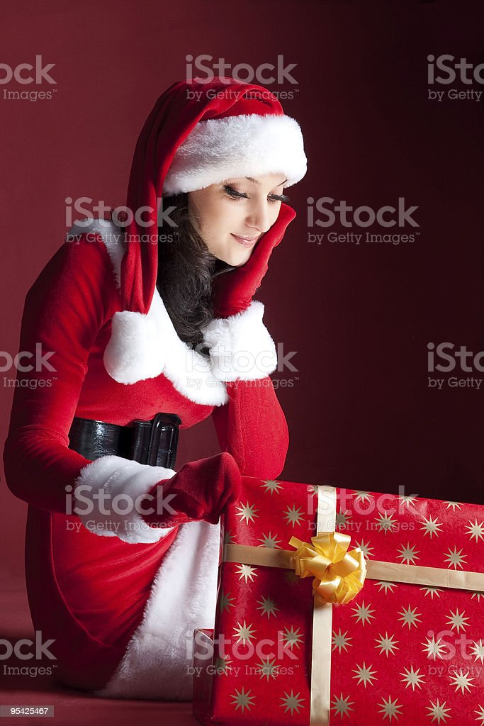 beautiful brunette in Christmas dress opens gift. royalty-free stock photo