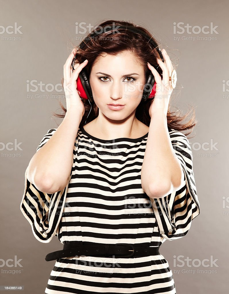Beautiful brunette listening to music on red headphones royalty-free stock photo