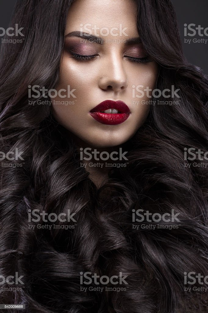 Beautiful brunette model: curls, classic makeup and red lips. The stock photo