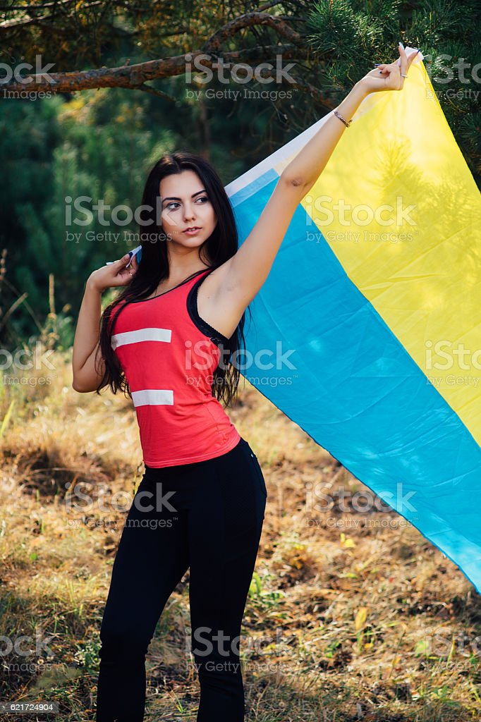 Beautiful brunette model posing in park with  flag of Ukraine stock photo