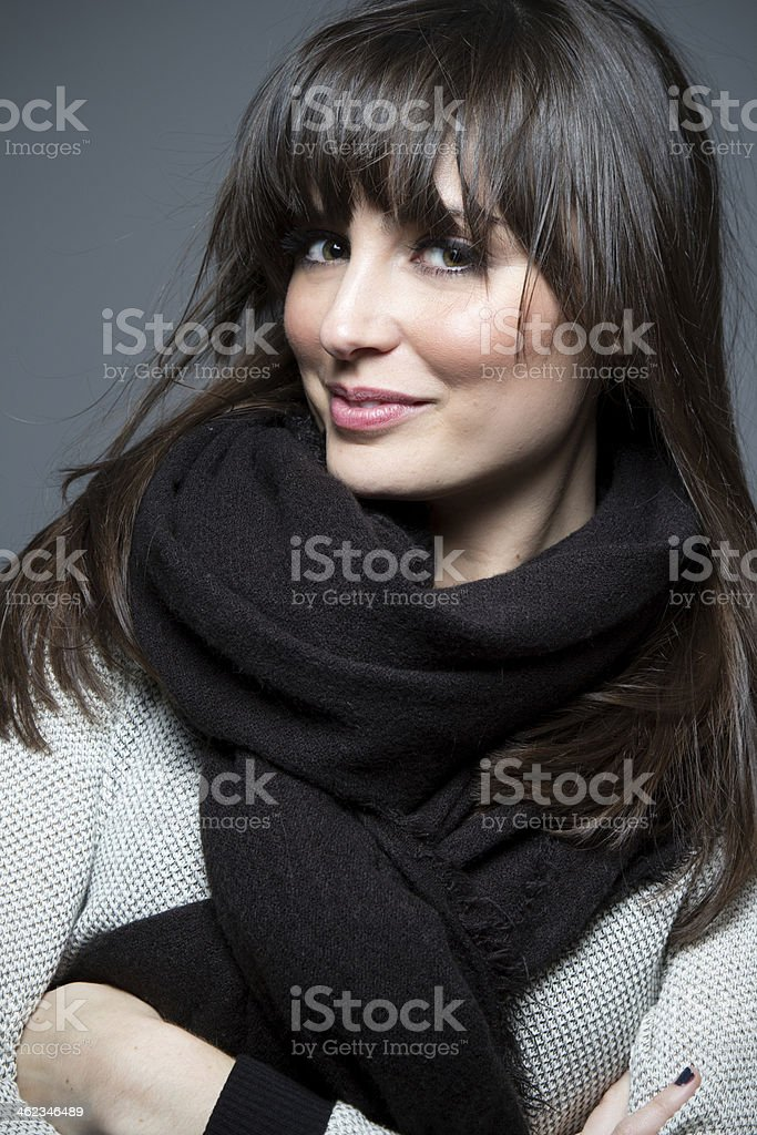 Beautiful brunette model wearing sweater and scarf. stock photo
