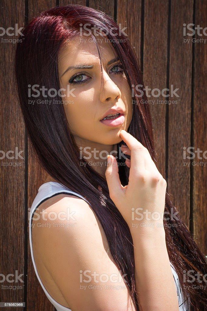 Beautiful brunette posing next to the wooden door stock photo