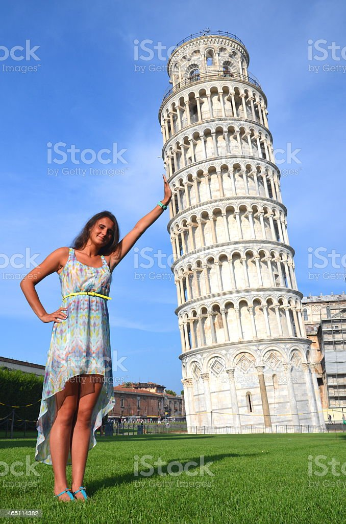 beautiful brunette tourist girl holding leaning tower in pisa, italy stock photo