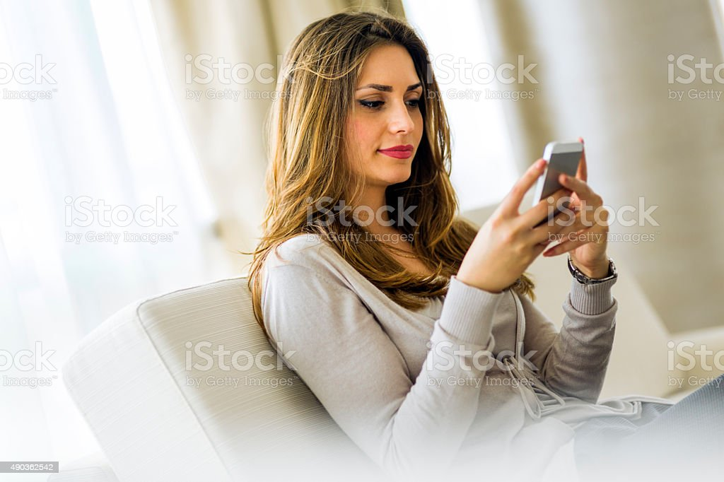 Beautiful brunette using a phone in a stylish house stock photo