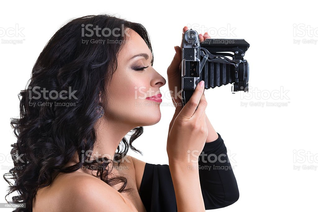 Beautiful brunette  woman holding a vintage camera isolated stock photo