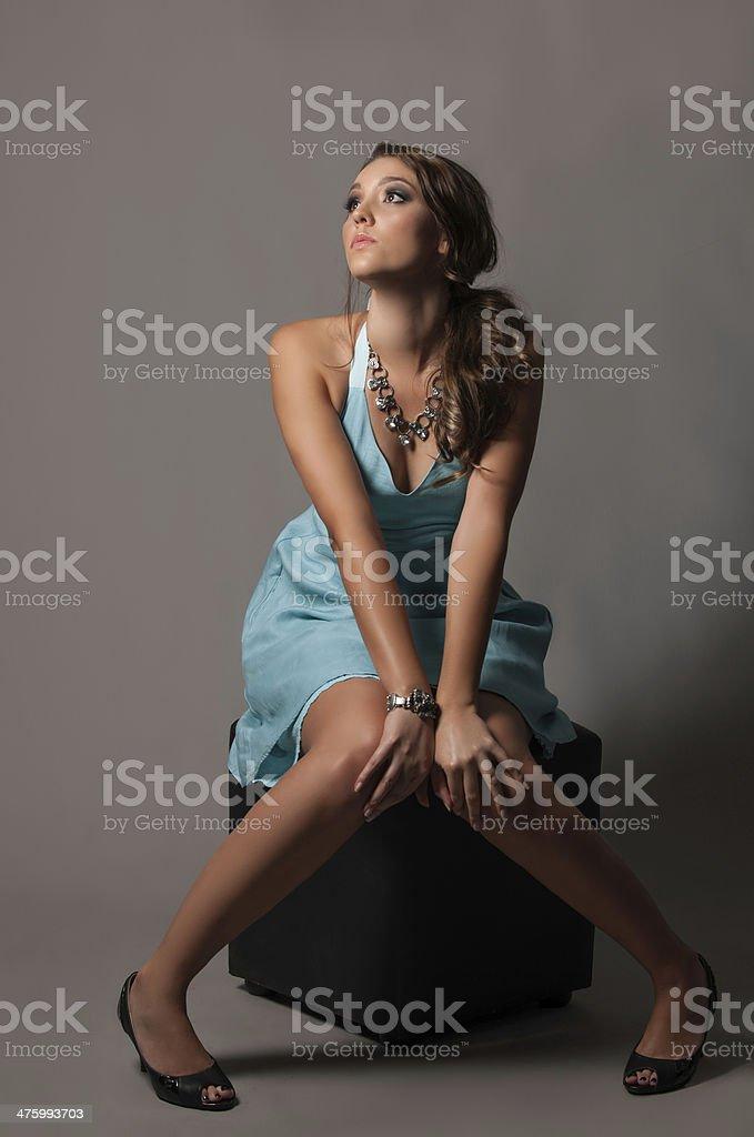 Beautiful brunette woman in blue dress gazing upwards stock photo
