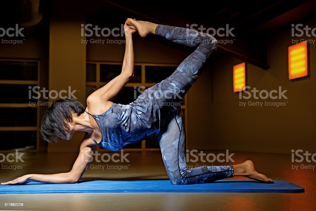 Beautiful brunette woman in yoga position at gym stock photo