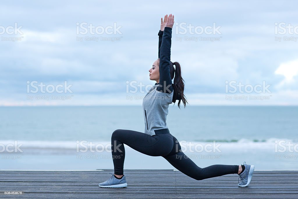 Beautiful brunette woman on a seafront wearing sports clothes stock photo