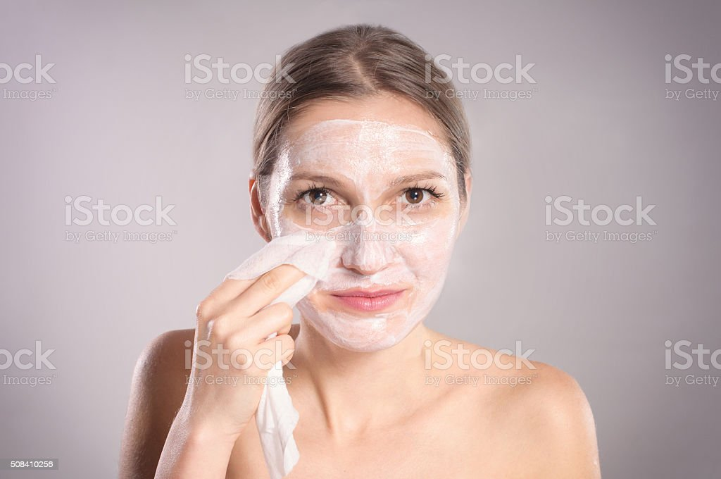 Beautiful brunette woman removing makeup from her face stock photo