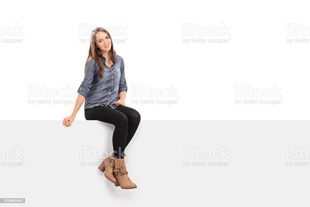 Beautiful brunette woman sitting on a panel stock photo
