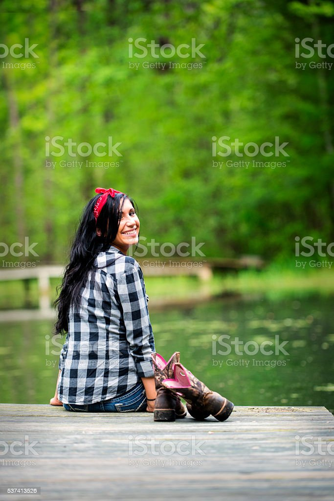 Beautiful Brunette Woman Sitting on Dock by the Pond stock photo