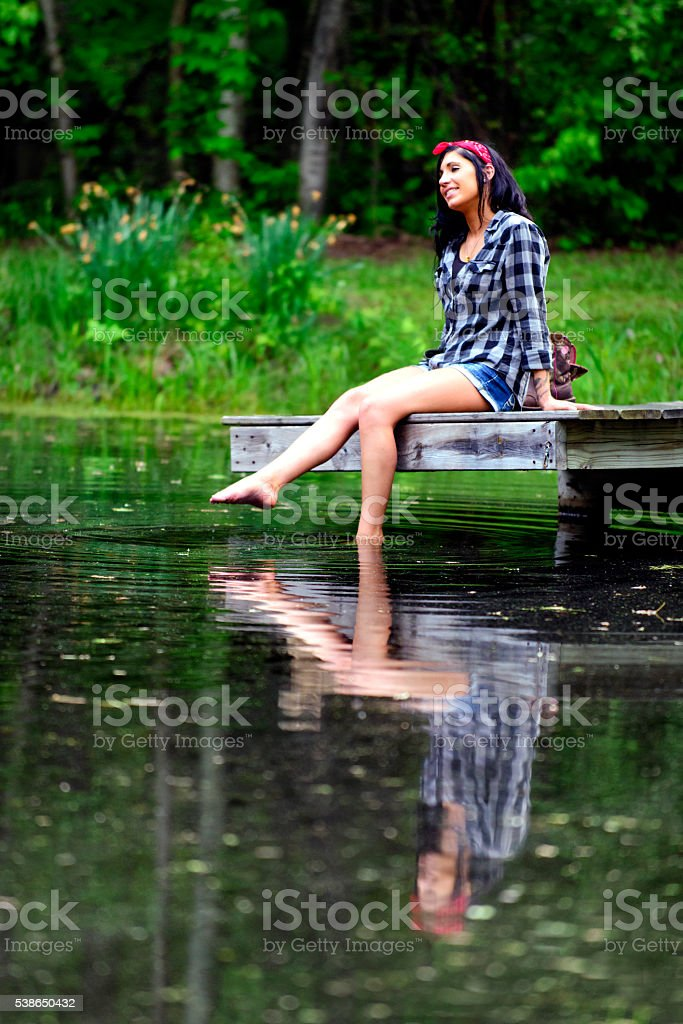 Beautiful Brunette Woman Sitting on Dock Feet in the Water stock photo