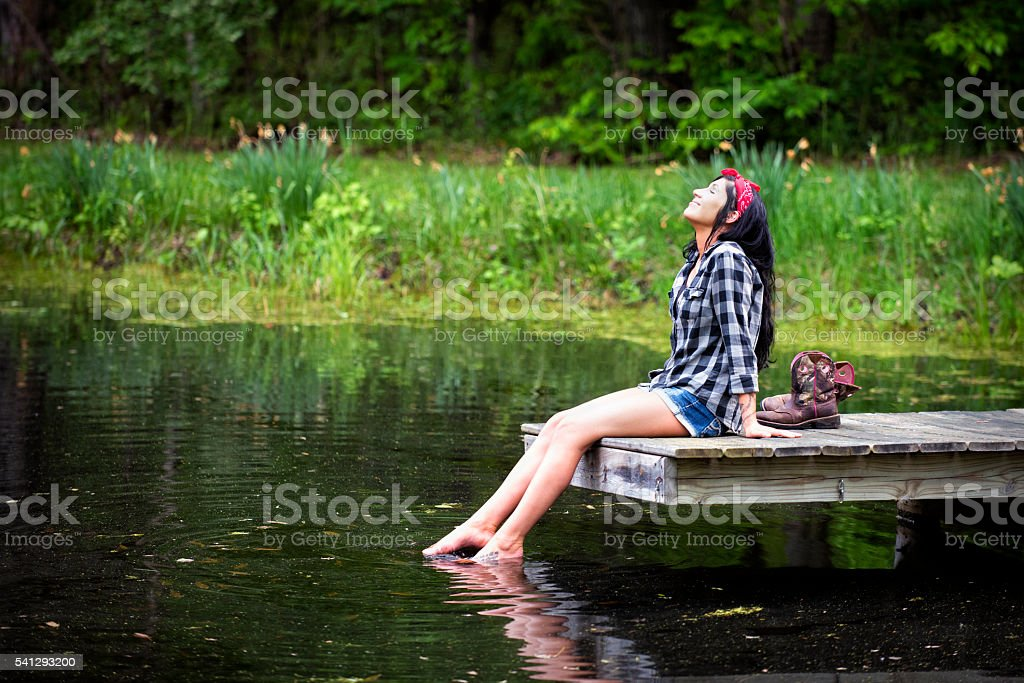 Beautiful Brunette Woman Sitting on Dock Feet in the Water stock photo