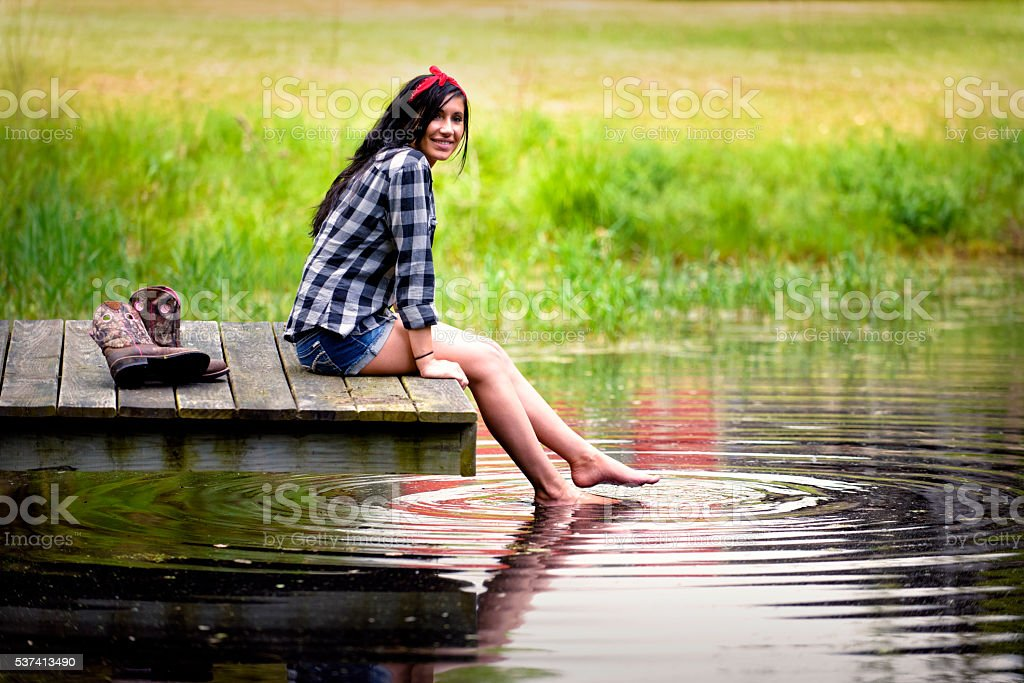 Beautiful Brunette Woman Sitting on Dock with Feet in Water stock photo