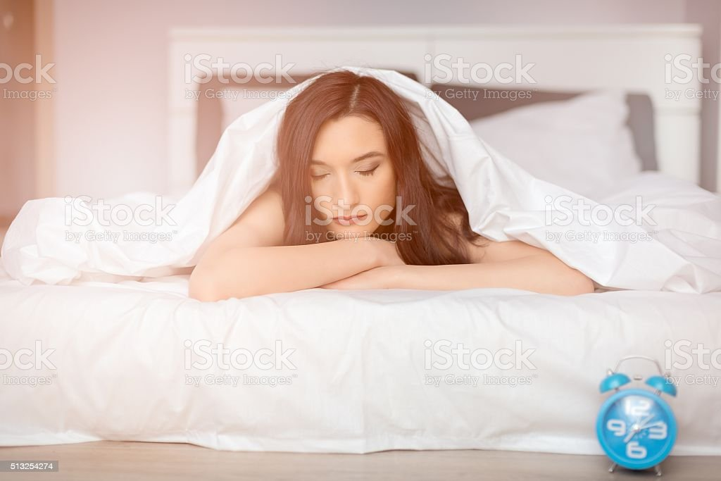 beautiful brunette woman sleeping on her stomach stock photo