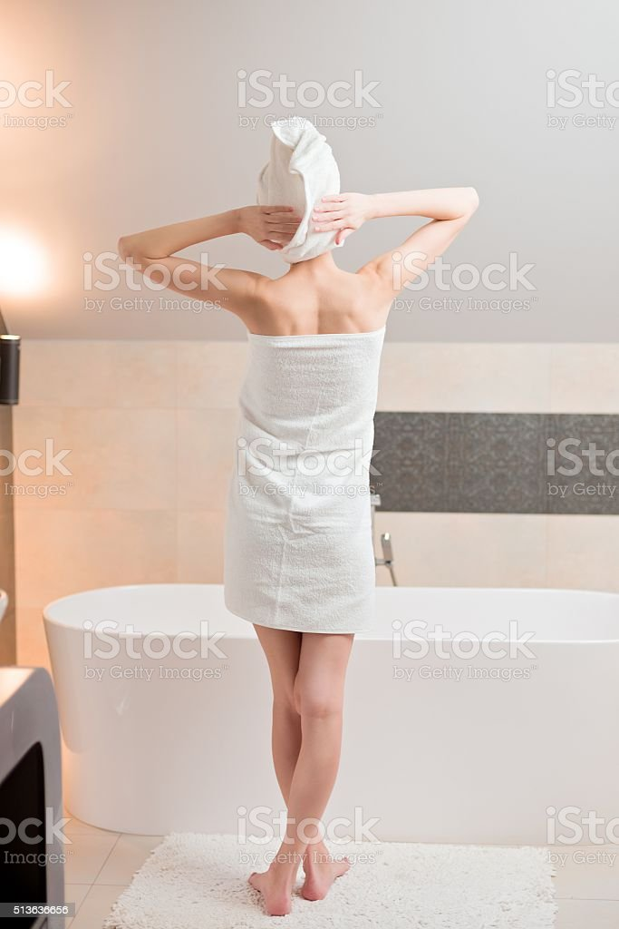 Beautiful brunette woman standing near bathtub. stock photo