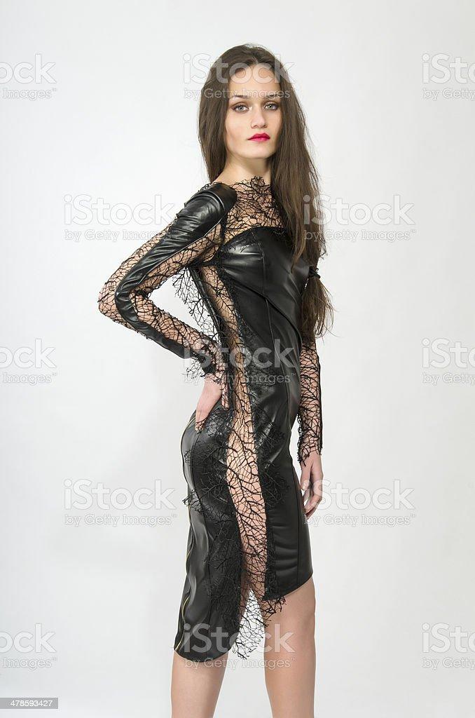 Beautiful brunette woman wearing a black leather dress stock photo