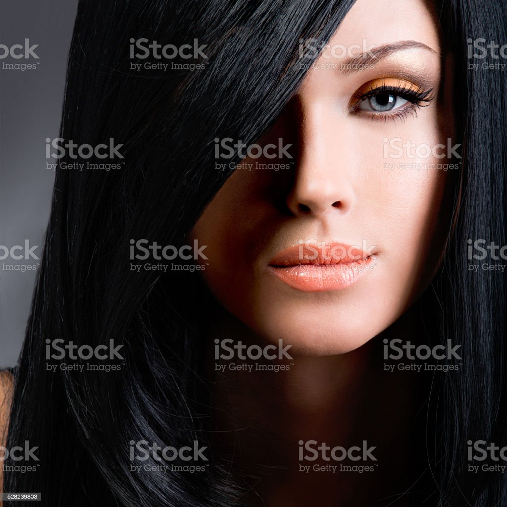 Beautiful brunette woman with long black straight hair stock photo