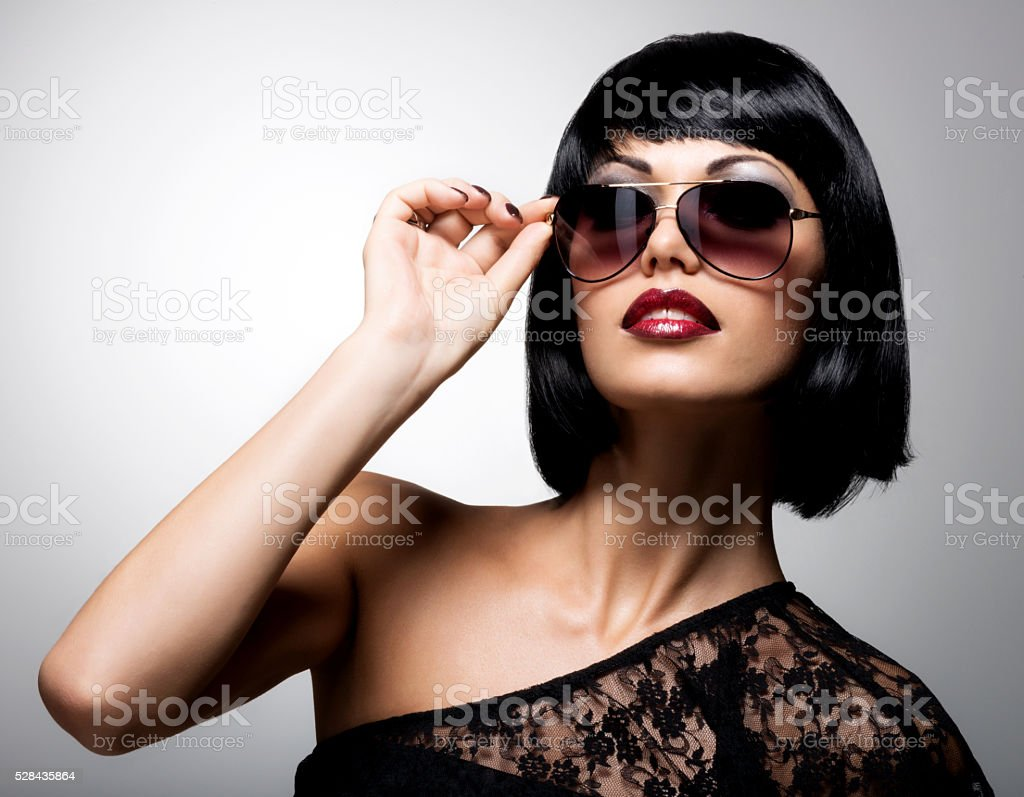 beautiful brunette woman with shot hairstyle in red sunglasses stock photo