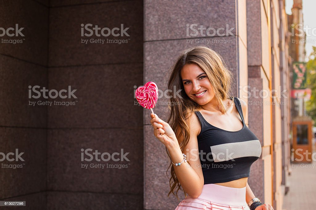 Beautiful brunette woman with sweet heart shaped candy stock photo