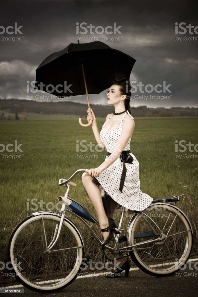 Beautiful Brunette Young Woman Riding Antique Bike in Stormy Weather stock photo