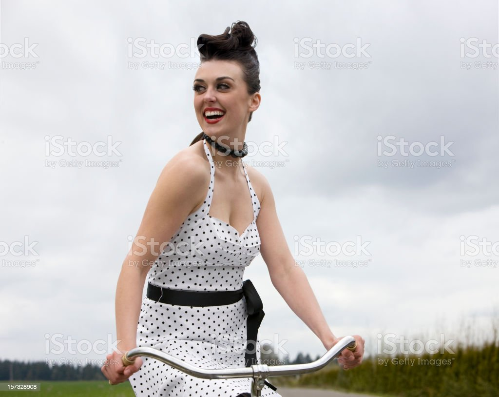 Beautiful Brunette Young Woman Riding Retro Bicycle in Dress Outdoors royalty-free stock photo