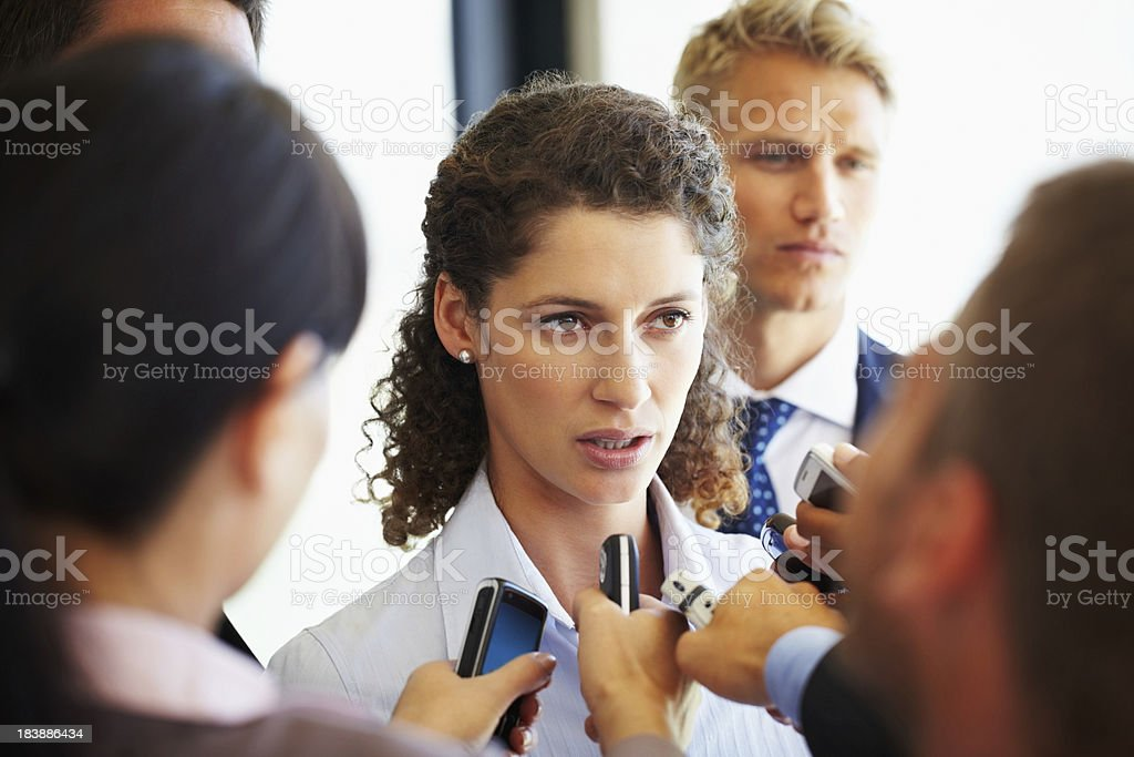 Beautiful business woman being questioned by journalists royalty-free stock photo