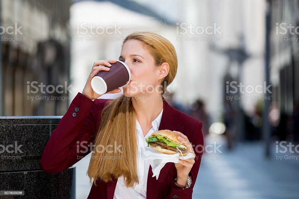Beautiful business woman having snack on the street. stock photo