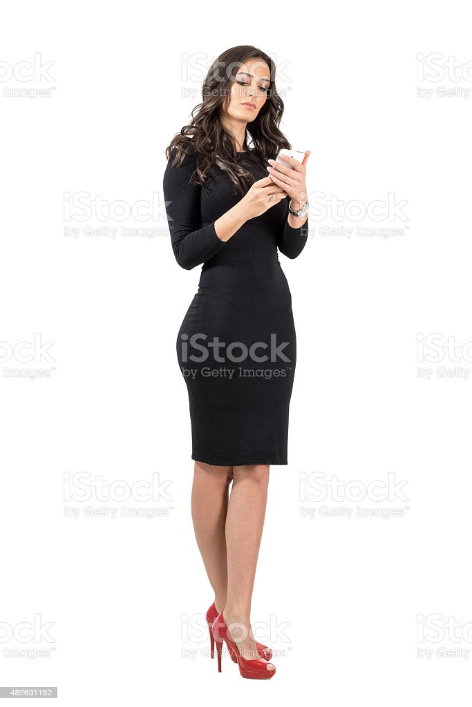Beautiful business woman in elegant black dress typing on smartphone stock photo