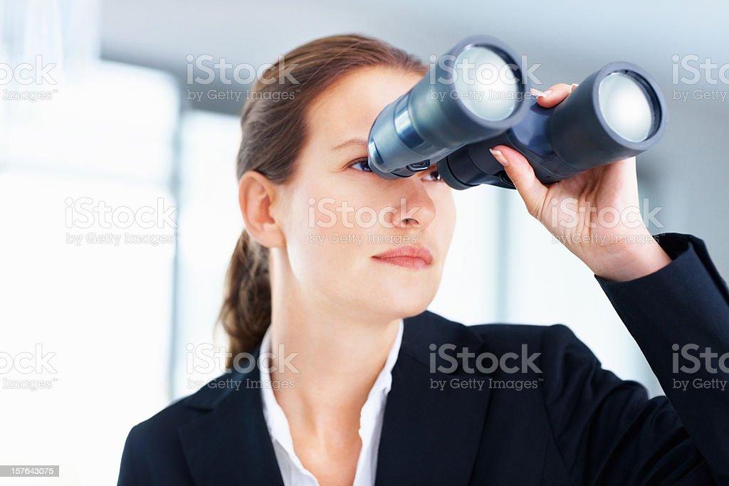 Beautiful business woman looking through binoculars royalty-free stock photo