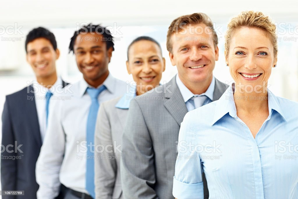 Beautiful business woman smiling with colleagues at the back royalty-free stock photo