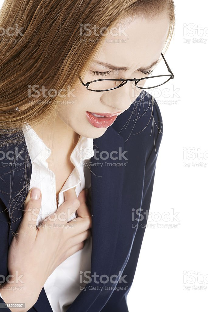 Beautiful business woman touching her chest, feeling unwell. stock photo