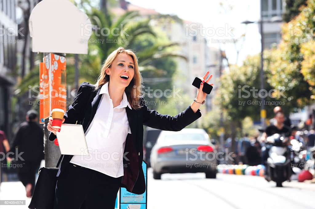 Beautiful businesswoman hailing taxi in street stock photo