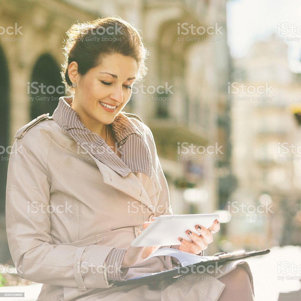 Beautiful businesswoman in the city using digital tablet stock photo