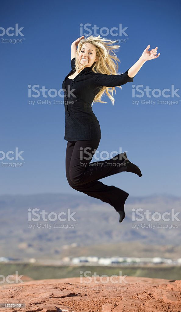 Beautiful Businesswoman Jumping for Joy in Desert royalty-free stock photo