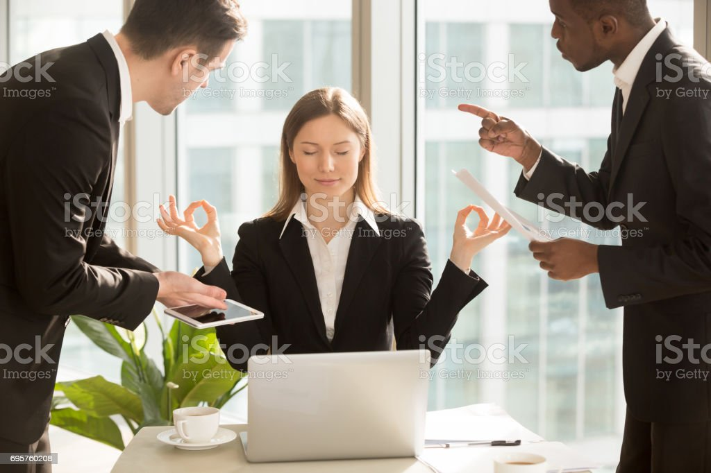 Beautiful businesswoman meditating at workplace, ignoring work and annoying colleagues stock photo