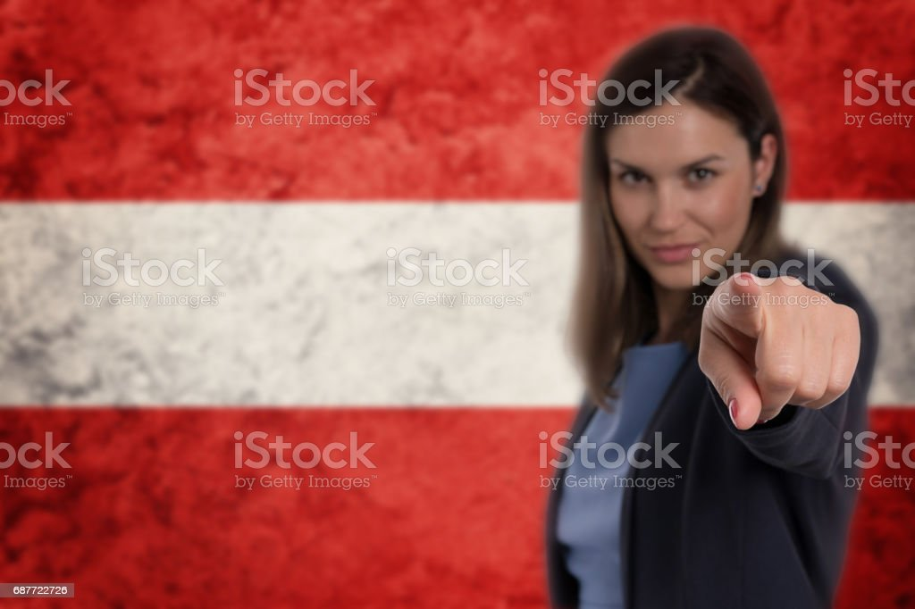 Beautiful businesswoman pointing her finger at you Austrian flag background. stock photo