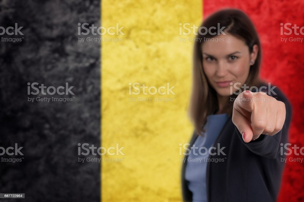 Beautiful businesswoman pointing her finger at you Belgian flag background. stock photo