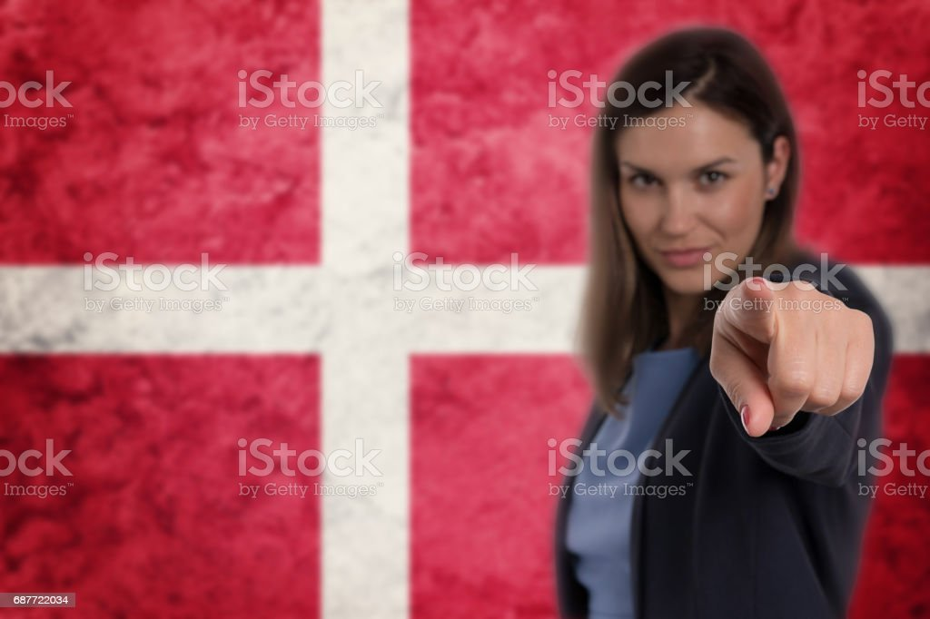 Beautiful businesswoman pointing her finger at you Danish flag background. stock photo