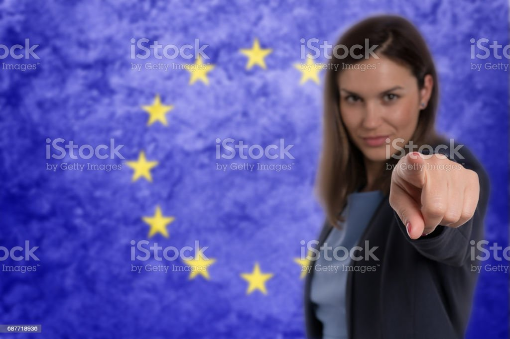 Beautiful businesswoman pointing her finger at you German flag background. stock photo
