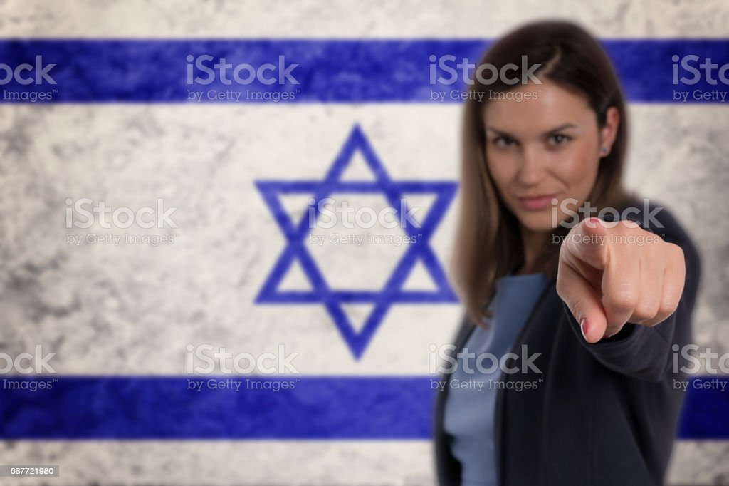 Beautiful businesswoman pointing her finger at you Israel flag background. stock photo